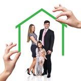 Soporte de la familia debajo de la casa verde Fotos de archivo libres de regalías