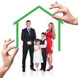 Soporte de la familia debajo de la casa verde Imagenes de archivo