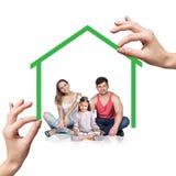 Soporte de la familia debajo de la casa verde Imagen de archivo libre de regalías