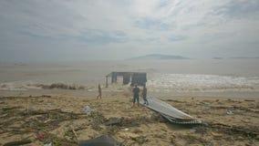 Soporte de la gente en la playa delante de la navegación quebrada del edificio en el mar
