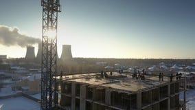Soporte de la gente de la visión aérea en el edificio contra salida del sol almacen de metraje de vídeo