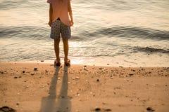 Soporte de la muchacha del fondo del viaje solamente en la playa que mira el SE hermoso Fotografía de archivo libre de regalías