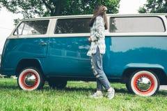 Soporte de la mujer cerca del minivan en tiempo de la lluvia Fotos de archivo