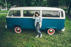 Soporte de la mujer cerca del minivan en tiempo de la lluvia Imagenes de archivo