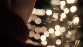 Soporte de la mujer con las luces del bokeh de la Navidad metrajes