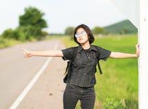 Soporte de la mujer con la mochila que hace autostop a lo largo de un camino Imágenes de archivo libres de regalías