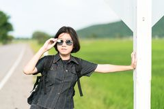 Soporte de la mujer con la mochila que hace autostop a lo largo de un camino Fotos de archivo