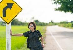 Soporte de la mujer con la mochila que hace autostop a lo largo de un camino Foto de archivo