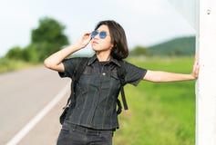 Soporte de la mujer con la mochila que hace autostop a lo largo de un camino Imagenes de archivo