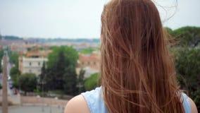 Soporte de la mujer en mirada de la plataforma de observación en el panorama de la ciudad Pelo del ` s de la muchacha que agita e metrajes