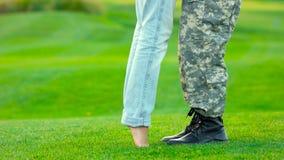 Soporte de la mujer en sus dedos del pie para besar a su novio del soldado metrajes