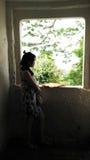 Soporte de la mujer joven en la ventana oscura Fotografía de archivo