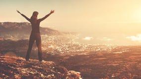 Soporte de la mujer joven encima de la montaña con las manos aumentadas