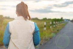 Soporte de la mujer joven solamente en el camino con el campo y la puesta del sol de hierba en e Fotos de archivo libres de regalías