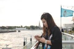 Soporte de la mujer joven solamente en la orilla y ella que miran el teléfono elegante Fotografía de archivo libre de regalías