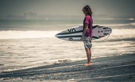 Soporte de la persona que practica surf en la playa con rvca del tablero Fotografía de archivo libre de regalías