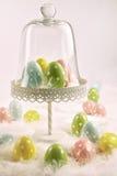 Soporte de la torta con los huevos y las plumas de Pascua Imagen de archivo libre de regalías