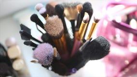 Soporte de las herramientas del maquillaje en la tabla Dispositivos cosméticos profesionales Cepillo y cosmético y otras herramie almacen de video