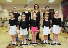 Soporte de las muchachas con el profesor del ballet Fotografía de archivo