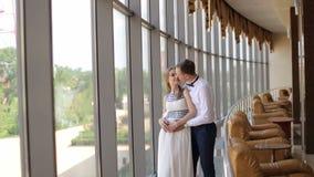Soporte de los pares que abraza cerca de ventanas panorámicas almacen de metraje de vídeo