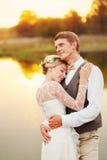 Soporte de los recienes casados delante de un lago Foto de archivo libre de regalías
