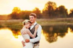 Soporte de los recienes casados delante de un lago Foto de archivo