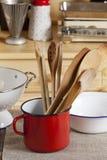 Soporte de los utensilios de cocinar en una tabla de cocina Foto de archivo