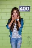 Soporte de pelo largo hermoso de la muchacha sorprendido cerca del greenbrick Foto de archivo libre de regalías