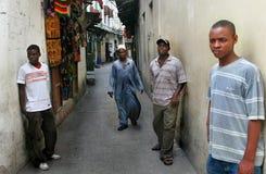 Soporte de piel morena joven de los africanos cerca de casas de las paredes en la remolque de piedra Fotografía de archivo libre de regalías