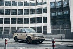 Soporte de Rover Range Rover de la tierra del coche cerca del edificio moderno en la ciudad de Moscú en el d3ia Fotografía de archivo