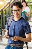 Soporte del estudiante masculino del retrato que sostiene la tableta Imagenes de archivo