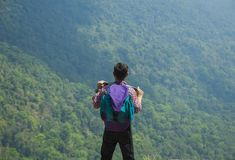 Soporte del hombre del Backpacker en viaje del acantilado sobre la montaña verde de la naturaleza Imagen de archivo libre de regalías