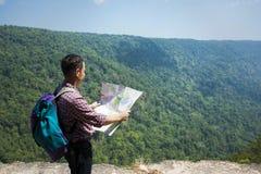 Soporte del hombre del Backpacker en viaje del acantilado sobre la montaña verde de la naturaleza Fotos de archivo