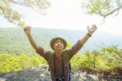 Soporte del hombre del Backpacker en viaje del acantilado sobre la montaña verde de la naturaleza Imagen de archivo