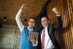 Soporte del hombre de negocios de dos asiáticos y mirada de la tableta, ellos alegres y celebrados el suyo acertado en la misión fotos de archivo libres de regalías
