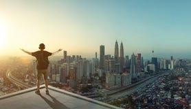 Soporte del hombre joven en el tejado que mira gran paisaje urbano Fotos de archivo