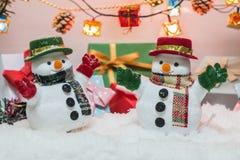 Soporte del muñeco de nieve entre la pila de nieve en la noche silenciosa con una bombilla, una Feliz Navidad y una noche del Año Imagenes de archivo