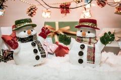 Soporte del muñeco de nieve entre la pila de nieve en la noche silenciosa con una bombilla, una Feliz Navidad y una noche del Año Fotografía de archivo libre de regalías