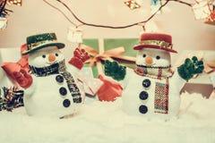 Soporte del muñeco de nieve entre la pila de nieve en la noche silenciosa con una bombilla, una Feliz Navidad y una noche del Año Imagen de archivo
