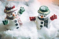 Soporte del muñeco de nieve entre la pila de nieve en la noche silenciosa con una bombilla, una Feliz Navidad y una noche del Año Fotos de archivo