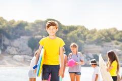 Soporte del muchacho en la playa con el tablero del cuerpo Imagen de archivo libre de regalías
