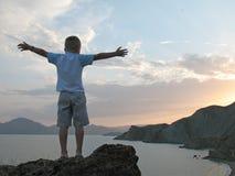 Soporte del muchacho en tapa de la montaña con las manos para arriba Fotografía de archivo