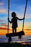 Soporte del niño en el oscilación en fondo colorido del cielo de la puesta del sol Fotos de archivo