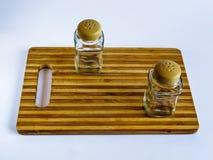 Soporte del pote de pimienta y de la coctelera de sal vacío en una tabla de cortar en un fondo blanco fotografía de archivo libre de regalías