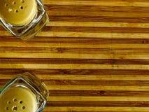 Soporte del pote de pimienta y de la coctelera de sal vacío en una tabla de cortar en un fondo blanco imágenes de archivo libres de regalías