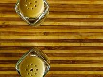Soporte del pote de pimienta y de la coctelera de sal vacío en una tabla de cortar en un fondo blanco imagen de archivo libre de regalías