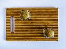 Soporte del pote de pimienta y de la coctelera de sal vacío en una tabla de cortar en un fondo blanco imagen de archivo