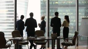 Soporte diverso del grupo de los empleados que habla por separado en el trabajo, vista posterior almacen de video
