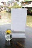 Soporte en blanco del menú con las flores del vaso de medida Foto de archivo