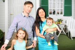 Soporte feliz de la familia de cuatro miembros cerca del pórtico de nuevo su cabaña Imagenes de archivo